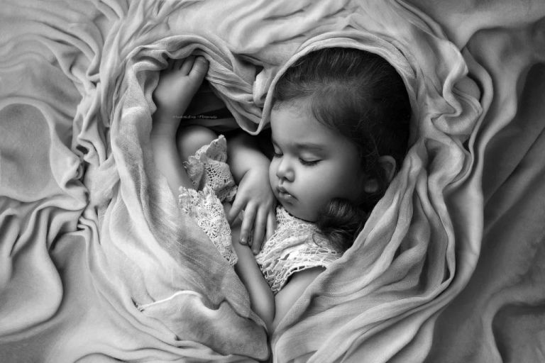 Sleeping toddler posed for newborn style photographs at 2.5 years old wrapped in a heart shaped blanket