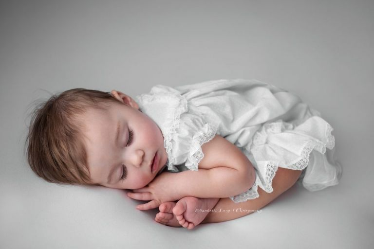 A toddler sleeps curled up on a white beanbag fabric