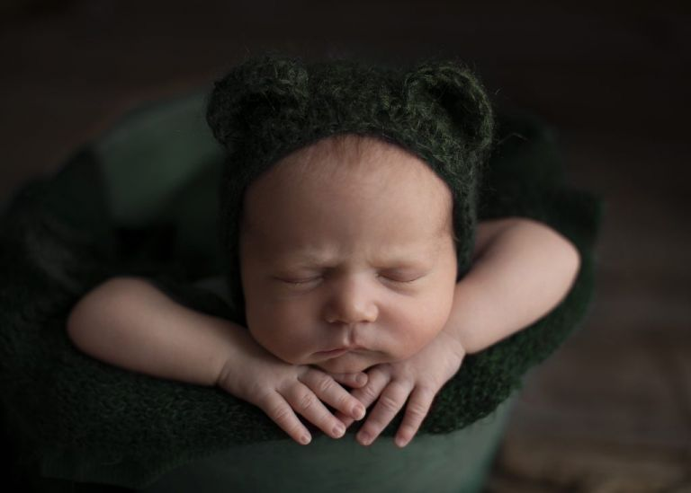 Newborn baby posed in a green bucket with matching green bear bonnet