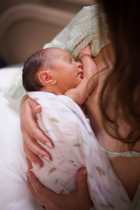 A mother holds her perfect new baby while wearing her hospital gown